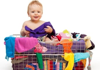 Happy smiling toddler in big basket with clothes