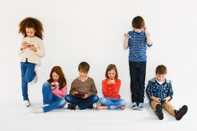 London, England, UK --- Children with different gadgets --- Image by © Dan Pangbourne/Image Source/Corbis